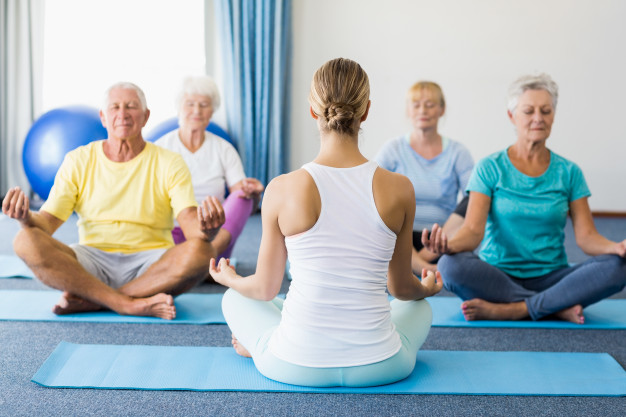 Group of senior adults meditating at an assisted living with memory care facility