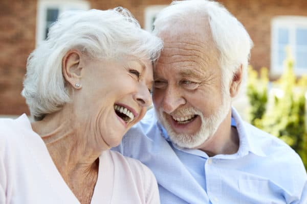 Retired Couple Sitting On Bench And Talking In Assisted Living Facility
