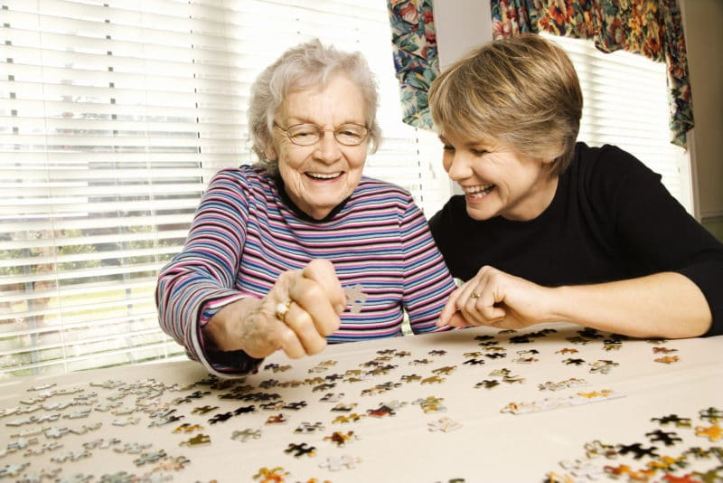Senior adult is playing puzzle at a senior living california community