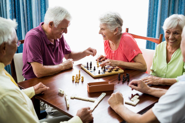 Senior adults playing board games in Rosewood assisted living in Fresno, CA