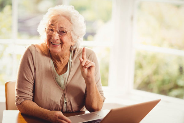 Smiling senior woman in front of her laptop