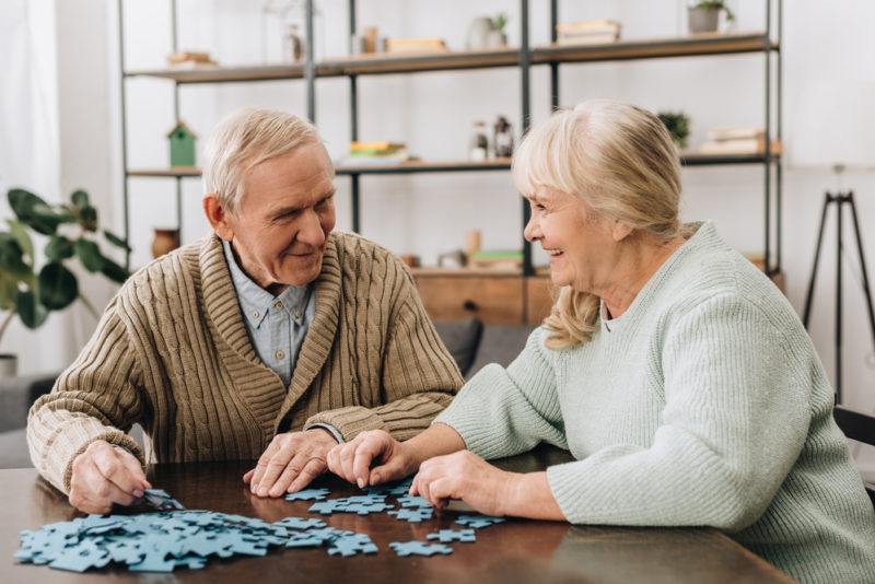 Older adults playing puzzle as part of their memory care activities